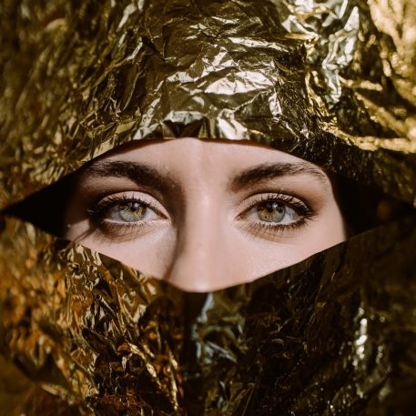 woman behind gold paper